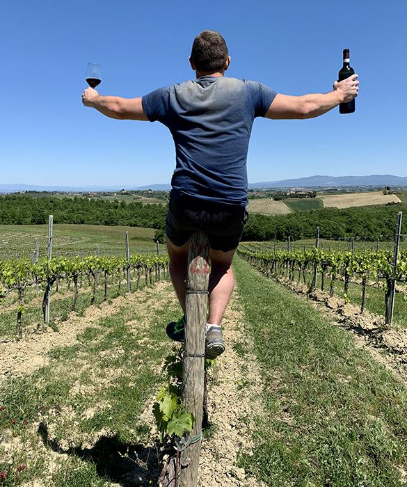 viticoltore su filare con bottiglia e calice di vino